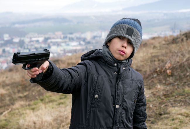 98375833 - young boy with angry face and gun