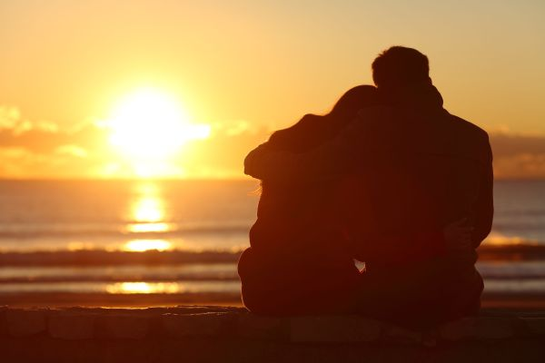 Couple watching sunset on the beach in winter