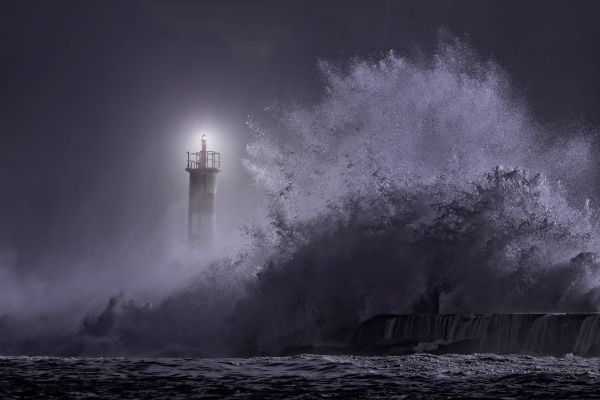 44976210 - river mouth lighthouse seeing big stormy sea wave at night